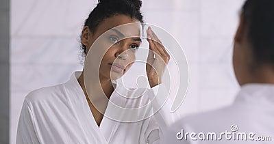 Μια υγιής χαμογελαστή αφρικανή κρατά το δέρμα προσώπου με καθαριστικό βαμβάκι απόθεμα βίντεο