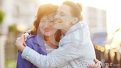 Μια ώριμη μητέρα και μια ενήλικη κόρη συναντήθηκαν στην οδό και αγκαλιάζουν Ευτυχής οικογένεια, συνοχή των γενεών μητέρες φιλμ μικρού μήκους