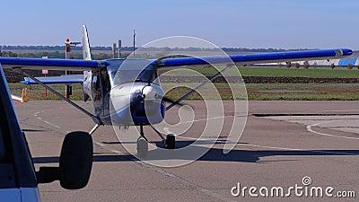 Μικρό ιδιωτικό αεροπλάνο με έναν περιστρεφόμενο προωστήρα που στέκεται στο χώρο στάθμευσης αεροσκαφών σε ένα μικρό αεροδρόμιο απόθεμα βίντεο