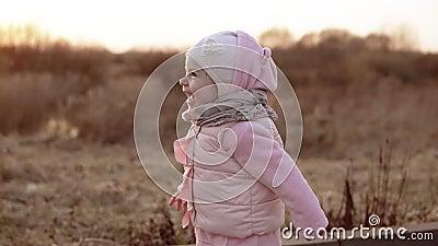 Μικρό κορίτσι που τρέχει και που γελά στο ηλιοβασίλεμα σε σε αργή κίνηση στο ρόδινο ιματισμό φιλμ μικρού μήκους