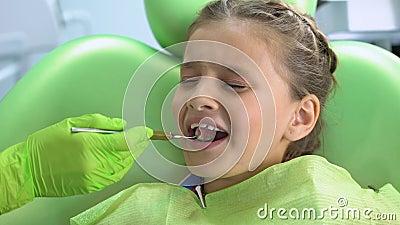 Μικρό κορίτσι φοβισμένο της οδοντικής εξέτασης με το στοματικό καθρέφτη, παιδαριώδης φόβος, πίεση απόθεμα βίντεο
