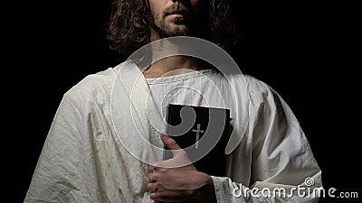 Μοναχός στην άσπρη τήβεννο που κρατά την ιερή Βίβλο στο σκοτεινό κλίμα, χριστιανισμός φιλμ μικρού μήκους