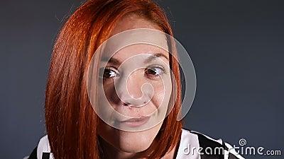 Μοντέρνη κοκκινομάλλης γυναίκα που εξετάζει τη κάμερα με την περιέργεια απόθεμα βίντεο