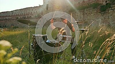 Μουσικός ντράμερ ντυμένος με μαύρα ρούχα, καπέλο, παίζοντας το σετ τυμπάνου και τα ποδηλατάκια απόθεμα βίντεο
