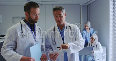 Μπροστινή όψη των Καυκάσιων ανδρών γιατρών που συζητούν πάνω από ψηφιακό δισκίο στο νοσοκομείο απόθεμα βίντεο