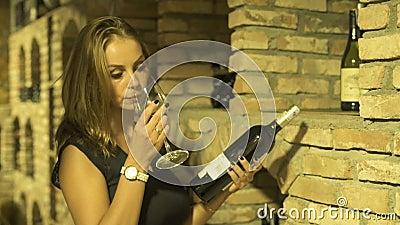Μυρίζοντας ποτήρι γυναικών winemaker του κόκκινου κρασιού και του κρατήματος του μπουκαλιού διαθέσιμου στο κελάρι Νέα γυναίκα που απόθεμα βίντεο