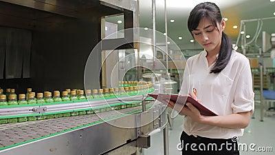 Νέα γυναίκα εργαζόμενοι στη βιομηχανία κατασκευής ποτών που ελέγχει την ποιότητα του προϊόντος απόθεμα βίντεο
