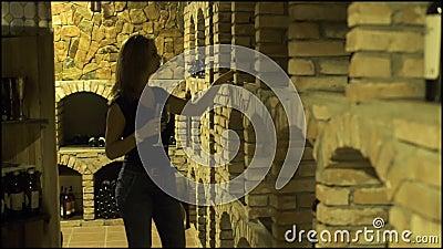 Νέα γυναίκα με το γυαλί κόκκινου κρασιού που φαίνεται μπουκάλι στο κελάρι Δοκιμάζοντας κόκκινο κρασί γυναικών winemaker στο παραδ φιλμ μικρού μήκους
