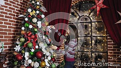 Νέα γυναίκα που διακοσμεί ένα χριστουγεννιάτικο δέντρο στο σπίτι απόθεμα βίντεο