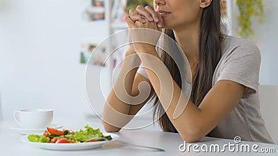 Νέα γυναίκα που προσεύχεται πρίν τρώει, που ζητά από το Θεό για να ευλογήσει τα τρόφιμα, πίστη, χριστιανισμός απόθεμα βίντεο