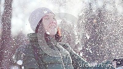 Νέα εύθυμη γυναίκα που πετά το χνουδωτό χιόνι στο πάρκο απόθεμα βίντεο