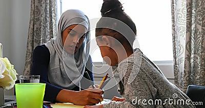 Νέα μητέρα που βοηθά την κόρη της με την εργασία της στον πίνακα στο σπίτι 4k απόθεμα βίντεο