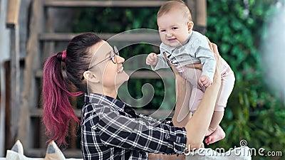 Νέα μητέρα hipster που αισθάνεται την ευχαρίστηση που παίζει με την λίγη χαριτωμένη μέση κινηματογράφηση σε πρώτο πλάνο κορών φιλμ μικρού μήκους