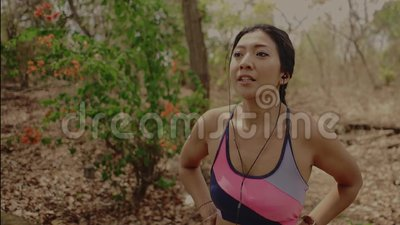Νέα όμορφη κουρασμένη και ιδρωμένη ασιατική γυναίκα δρομέων που αναπνέει και που δροσίζει μακριά μετά από σκληρά να τρέξει workou απόθεμα βίντεο
