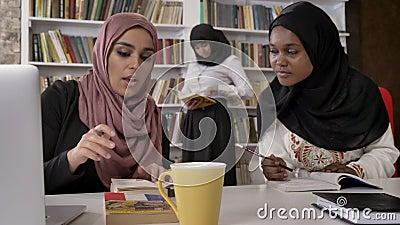 Νέες μουσουλμανικές γυναίκες στο hijab που εξηγεί κάτι στις μαύρες γυναίκες στο hijab, που μελετά στη βιβλιοθήκη και που προετοιμ απόθεμα βίντεο