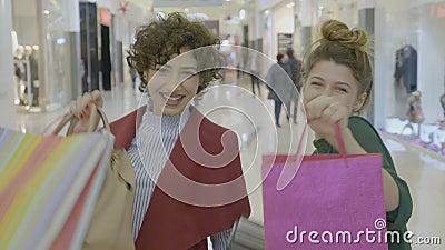 Νέοι θηλυκοί επιχειρηματίες που εκφράζουν την ευτυχία τους με την παρουσίαση τσαντών αγορών στη κάμερα μετά από να αγοράσει τα νέ φιλμ μικρού μήκους