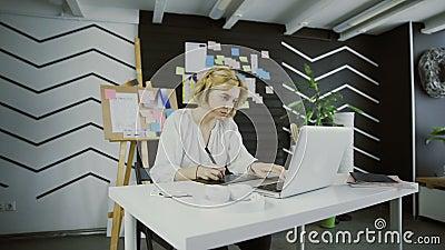 Νέος γραφικός σχεδιαστής με την κοντή τρίχα που λειτουργεί στον υπολογιστή που χρησιμοποιεί την ταμπλέτα φιλμ μικρού μήκους