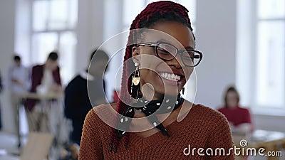 Νέος ευτυχής αφρικανικός δημιουργικός σχεδιαστής, επαγγελματική επιτυχής επιχειρησιακή γυναίκα eyeglasses που χαμογελούν χαρωπά σ απόθεμα βίντεο