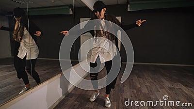 Νέος θηλυκός χορευτής στο άσπρο πουκάμισο, το μαύρο παντελόνι και τη μαύρη ΚΑΠ που παρουσιάζουν στην τζαζ σύγχρονο χορό Το κορίτσ φιλμ μικρού μήκους