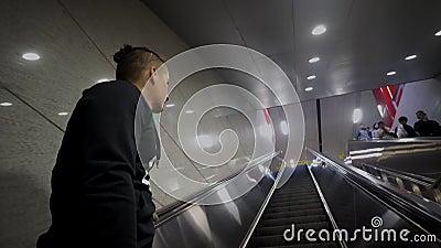 Νέο καυκάσιο άτομο που κινείται επάνω σε μια κυλιόμενη σκάλα στον αερολιμένα, υπόγειος φιλμ μικρού μήκους