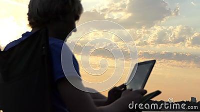 Νέο Blogger κάθεται σε μια έδρα και εξετάζει την ταμπλέτα του στο ηλιοβασίλεμα στην slo-Mo φιλμ μικρού μήκους