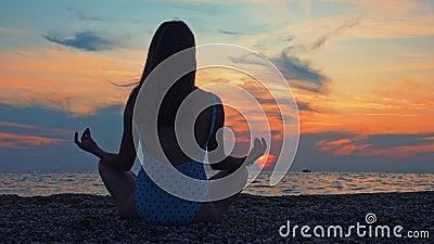 Νεαρές γυναίκες εξασκούν γιόγκα στη θάλασσα ή στον ωκεανό κατά το ηλιοβασίλεμα απόθεμα βίντεο