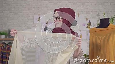 Νεαρές μουσουλμάνες σχεδιάστριες μόδας με εθνικές μαντίλες σε γυαλιά που δουλεύουν με ύφασμα αργά απόθεμα βίντεο
