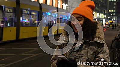 Νεαρή έφηβη χρησιμοποιεί το κινητό της το βράδυ με τραμ από το σταθμό Alexanderplatz, Βερολίνο, Γερμανία απόθεμα βίντεο