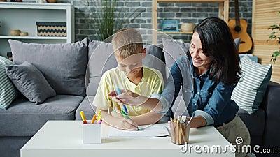 Νεαρή γυναίκα και χαρούμενο παιδί ζωγραφίζουν στο σπίτι δεμένοι απολαμβάνοντας χόμπι απόθεμα βίντεο