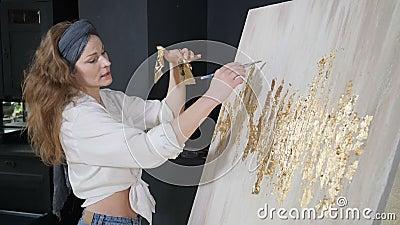 Νεαρή γυναίκα καλλιτέχνης που εφαρμόζει φύλλα χρυσού στο γραφικό της Ο καλλιτέχνης διακοσμεί εικόνα με ένα μικρό φύλλο χρυσού σχο φιλμ μικρού μήκους