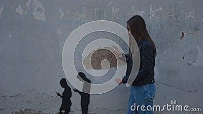 Νεαρή γυναίκα κοιτάζει το τηλέφωνο και επαναλαμβάνει την εικόνα στον τοίχο: δύο άτομα πάνε με το τηλέφωνο στα χέρια φιλμ μικρού μήκους
