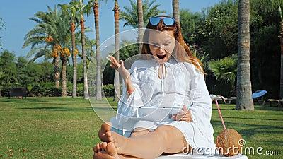 Νεαρή γυναίκα χαίρεται και γιορτάζει την επιτυχία, ενώ χρησιμοποιεί tablet κατά τη διάρκεια διακοπών στο θέρετρο απόθεμα βίντεο
