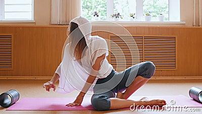 Νεαρή λεπτή γυναίκα με λευκό πουκάμισο με βοηθητικό πόδι κάτω από το πόδι για να τεντωθεί στο χωρισμένο απόθεμα βίντεο