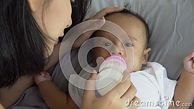 Νεαρή μητέρα που ταΐζει γάλα στο μωρό και φιλάει στο μέτωπο φιλμ μικρού μήκους