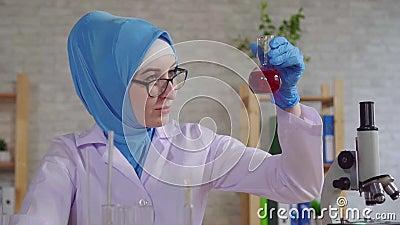 Νεαρή μουσουλμάνα γυναίκα επιστημονικός χημικός βοηθός στο εθνικό κασκόλ που εργάζεται στο εργαστήριο αργεί απόθεμα βίντεο