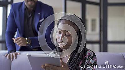 Νεαρή όμορφη Αφροαμερικανή γυναίκα με αφρικανικά χοιρίδια που κάθεται στο σπίτι δουλεύοντας με το tablet της Το κορίτσι που την κ απόθεμα βίντεο