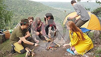 Νεαροί πεζοπόροι περνούν χρόνο στο στρατόπεδο, ετοιμάζουν φαγητό, το σαββατοκύριακο με φίλους απόθεμα βίντεο