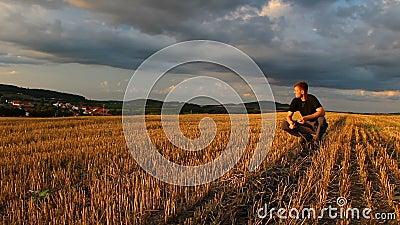 Νεαρός άνδρας κάθεται, παίζει με καλαμπόκι σε κουρελιασμένο χωράφι με δραματικό ουρανό το ηλιοβασίλεμα, Τσεχική δημοκρατία απόθεμα βίντεο