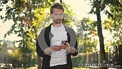 Νεαρός άνδρας που παίρνει το smartphone από την τσέπη και απόθεμα βίντεο