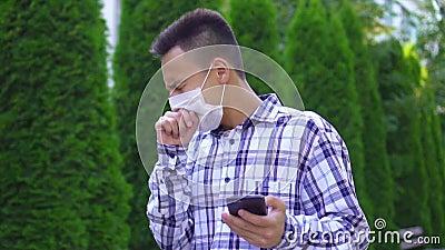 Νεαρός Ασιάτης με ιατρική μάσκα στο πρόσωπό του περνάει από το πάρκο βήχοντας και χρησιμοποιεί ένα smartphone slow mo απόθεμα βίντεο