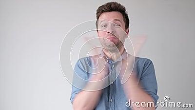 Νεαρός Καυκάσιος άνδρας χειροκροτά, ενθουσιασμένος με τις ειδήσεις φιλμ μικρού μήκους