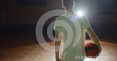 Νεαρός Καυκάσιος μπασκετμπολίστας ετοιμάζεται να πάει στα παρασκήνια, σκούρα σιλουέτα, αχτίδα φωτός μπάλα εμπιστοσύνης απόθεμα βίντεο