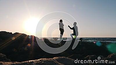 Νεαρός ντροπαλός άντρας κάνει μια προσφορά στην αγαπημένη του κοπέλα στην ακτή στο ηλιοβασίλεμα Ελκυστικός άντρας που στέκεται στ φιλμ μικρού μήκους