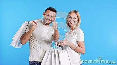 Νεαρό ευτυχισμένο ζευγάρι που κρατά τσάντες για ψώνια, άνδρας που δείχνει το σήμα επιδοκιμασίας στο μπλε φόντο απόθεμα βίντεο
