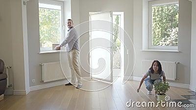 Νεαρό ζευγάρι από τον Καύκασο που μπαίνει στο νέο τους σπίτι και φυτό Η ευτυχισμένη οικογένεια αγκαλιάζεται σαν να κινείται σε έν απόθεμα βίντεο