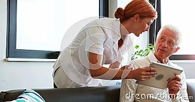 Νοσοκόμα και ανώτερος υπομονετικός χρησιμοποιώντας υπολογιστής ταμπλετών απόθεμα βίντεο