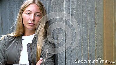 Ξανθιά νεαρή γυναίκα που κοιτάζει λυπημένη ή σκεπτόμενη φορώντας ένα πράσινο μπουφάν σε αστικό αστικό περιβάλλον απόθεμα βίντεο