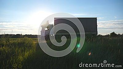 Οδήγηση φορτηγών σε μια εθνική οδό με τη φλόγα ήλιων στο υπόβαθρο Γύροι φορτηγών μέσω της επαρχίας με το όμορφο τοπίο φιλμ μικρού μήκους