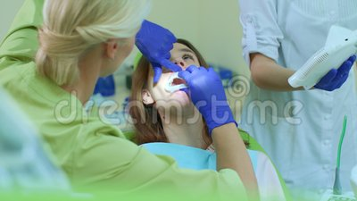 Οδοντίατρος με το βοηθητικό προετοιμαζόμενο κορίτσι για τη λεύκανση των δοντιών Λεύκανση της διαδικασίας απόθεμα βίντεο