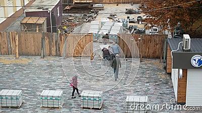 οδός Khlebnaya, πόλη Zhytomyr, Ουκρανία - 04 10 2019: κατασκευαστές σύρετε το φορτίο πλάκες για επικάλυψη Κτίριο φιλμ μικρού μήκους